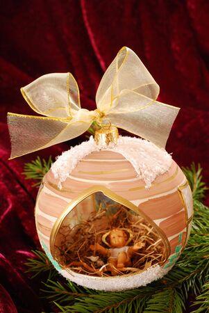christmas ball with Jesus figurine lying on hay inside  on burgundy velvet background photo