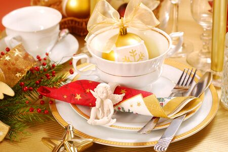 finery: decoration of christmas table with angel in  white and golden colors Stock Photo