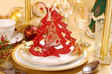 christmas table decoration with paper christmas tree shape on plate in red,golden and white colors photo