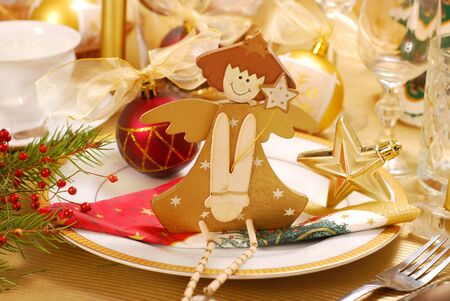 christmas table decoration with wooden angel on plate in golden and white colors photo