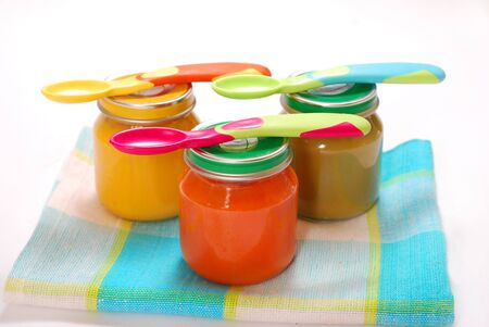 jars of various baby food and spoons isolated on white  Banco de Imagens