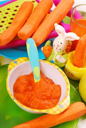 baby food: bowl of fresh grated carrot as homemade baby food Stock Photo