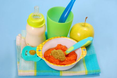 bowl of fresh grated carrot and green peas puree and bottle of milk as homemade baby food photo