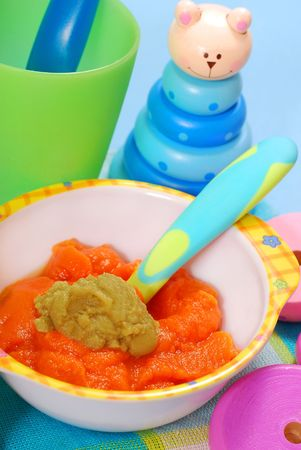pap: bowl of fresh grated carrot and green peas puree as homemade baby food