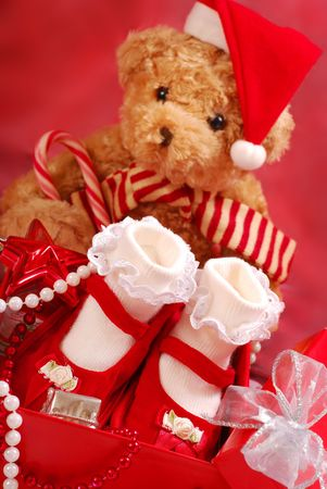the first step: red baby shoes with white socks for little girl as christmas  gift  and teddy bear  Stock Photo