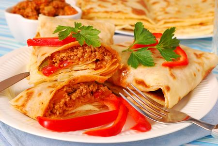 pancakes stuffed with minced meat and vegetables in bolognese sauce photo