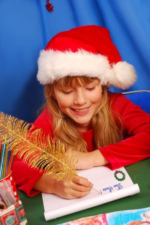 young girl in santa`s hat writing a letter to santa  by golden feather pen  photo