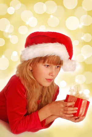 young girl in santa`s hat holding small  christmas gift on shining background photo