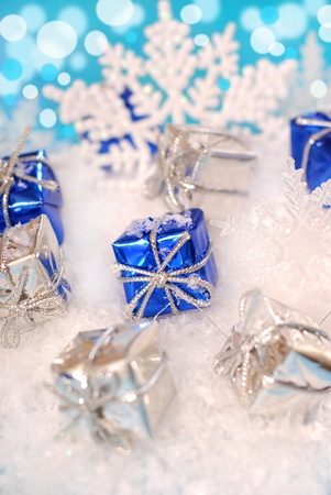 small christmas gift boxes lying  on snow  with shining effect in background photo