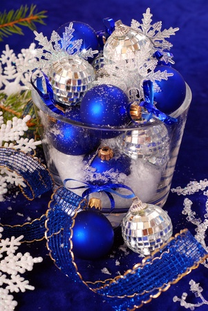 balls deep: christmas balls with snowflakes in glass vase  on deep blue background