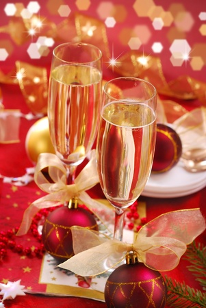 champagne glasses on festive table in red and golden colors photo