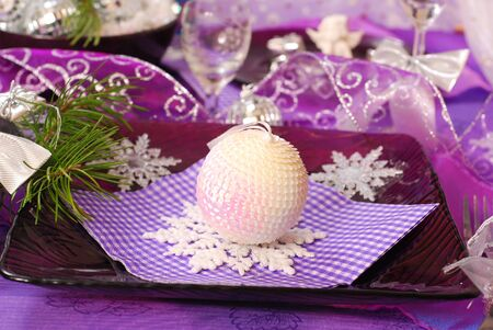 glamour christmas table decoration in purple color with shining ball and snowflakes on glass plate photo