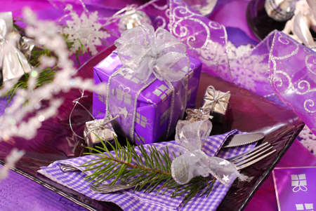 glamour christmas table decoration in purple color with gift box on glass plate photo