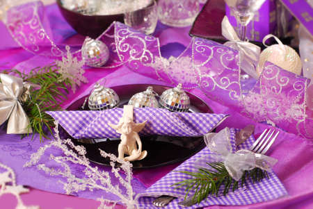 glamour christmas table decoration in purple color with angel on glass plate photo