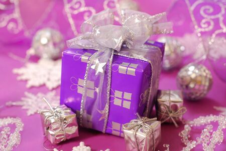 christmas gift box in purple color with silver ribbon on pink background photo