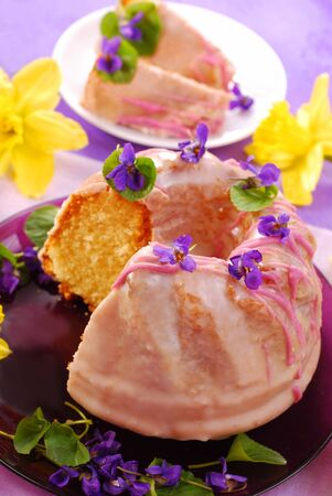 traditional vanilla ring cake with icing and violets decoration for easter photo