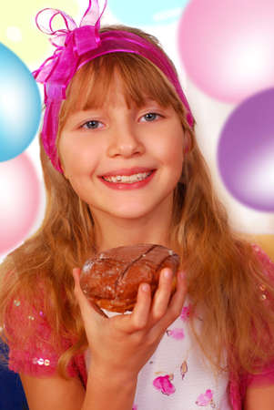 happy young girl eating donut on the party Stock Photo - 8640504