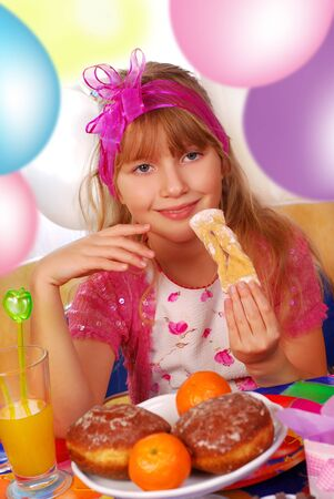 happy young girl eating cookies on the party photo