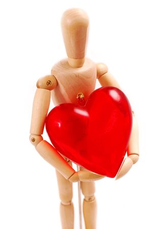 wooden man figure holding in hands big red heart isolated on white photo