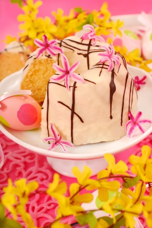 almond ring cake poured white and dark chocolate on easter table in pink color photo