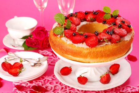 yeast ring cake with fresh strawberries and blueberries on pink background photo