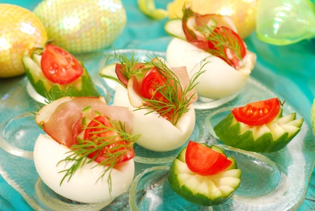 eggs stuffed with parma ham,cucumber,tomato and mayonnaise as appetizer for easter photo