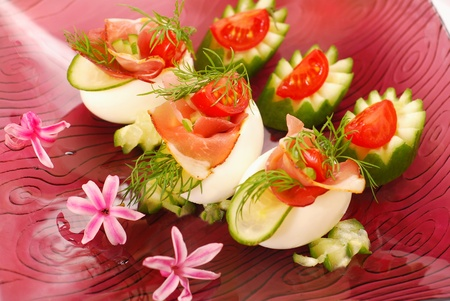 prosciutto: eggs stuffed with parma ham,cucumber,tomato and mayonnaise as appetizer for easter