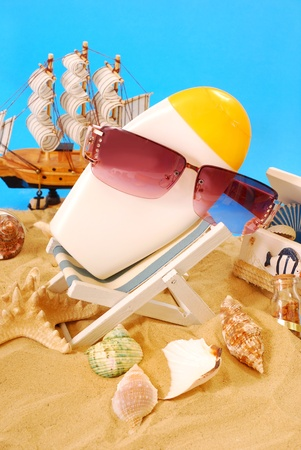 suntan lotion bottle wearing sunglasses lying on deckchair on the beach photo