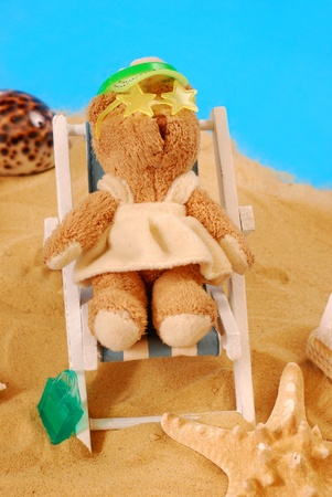funny scene with little teddy bear relaxing on the beach lying on deckchair Stock Photo - 8972868