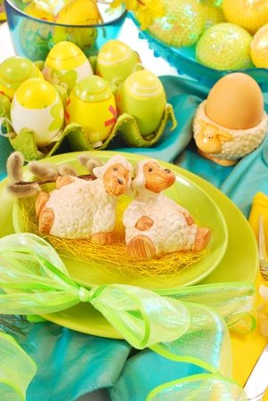 easter table decoration with two lambs figurines on  plate, all in turquoise,green and yellow colors photo