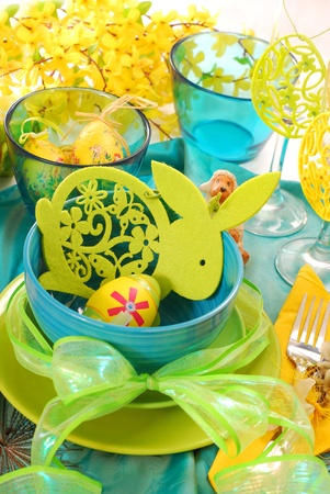 easter table decoration with felt rabbit in bowl in turquoise,green and yellow colors photo