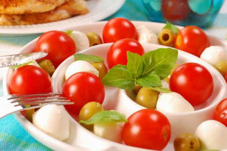 insalata caprese italiano con mozzarella, pomodoro, olive e basilico sul piatto di forma ricciolo Archivio Fotografico - 9047823