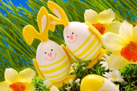 easter decoration with two eggs in bunny shape standing in grass  photo