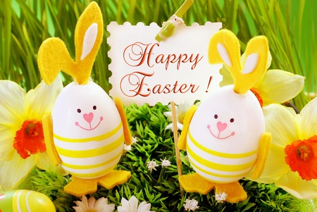 easter decoration with funny rabbit  shape eggs  standing in grass and holding banner with greetings photo