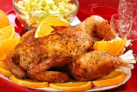 oven chicken: plate with delicious  roasted whole chicken with oranges for party