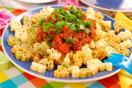 three colors pasta in animal shape and minced meat with vegetables as spaghetti bolognese for child`s dinner photo