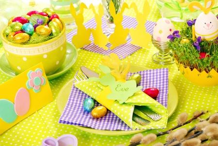 Ostern Tischdekoration in grün, violett und gelben Farben Standard-Bild