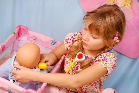 little blonde girl: little girl playing the doctor with her newborn baby doll in room