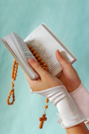 hands of the girl going to the First Holy Communion keeping a  prayer book and a  rosary on blue backgroun Stock Photo - 9269280