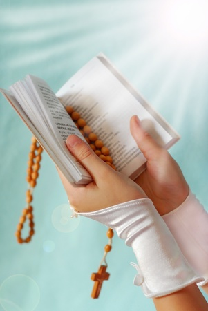 rosary: hands of the girl going to the First Holy Communion keeping a  prayer book and a  rosary on blue background with rays effect