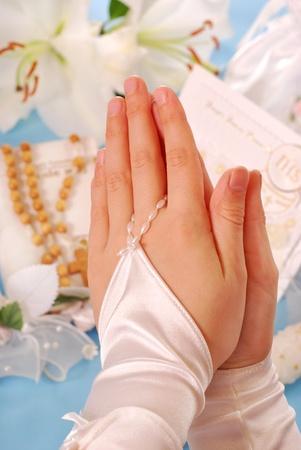 prima comunione: mani della ragazza per la prima comunione in amen e pregando in corso