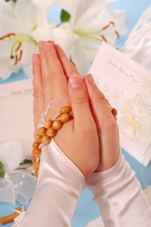hands of the girl going to the First Holy Communion set in amen and  praying with a  rosary  photo