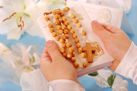 first communion: mains de la jeune fille va � la premi�re Sainte Communion gardant un livre de pri�res et un rosaire