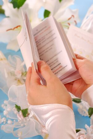 hands of the girl going to the First Holy Communion keeping a  prayer book  photo