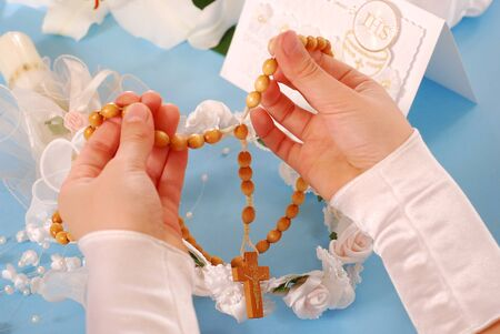 hands of the girl going to the First Holy Communion praying with wooden rosary  photo