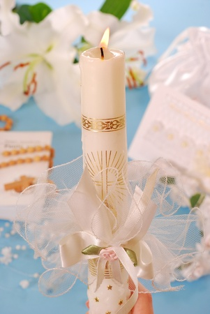 white candle with decoration for first holy communion on blue background photo