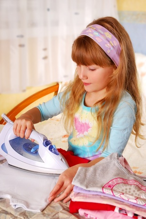 little girl helping her mother with ironing baby clothes photo
