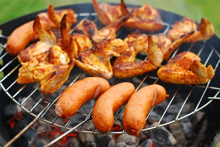 pork sausage: pork sausages  and chicken wings on smoking grill in the garden Stock Photo