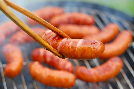 pork sausages on smoking grill in the garden Stock Photo