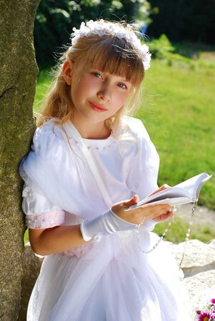 portret van bidden meisje in witte jurk en krans, naar de eerste heilige communie poseren in park Stockfoto